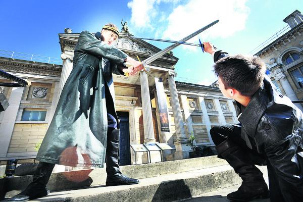 Alex Cowan, left, as King Arthur fights with Lancelot, played by Dan Blick on the steps of the Ashmolean