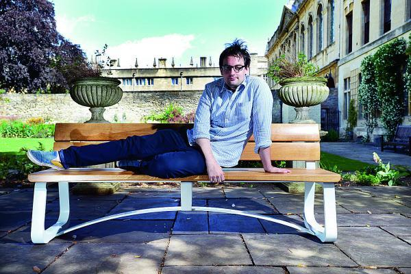 Tom Parfitt, who won a competition last year, with his benches now being installed at Queen's College, Oxford
