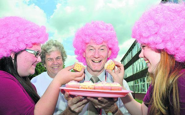 Bicester Community College's head of House Blenheim, Alistair McAulay, is fed cakes by, from left, Shania Mitchell, 14, Patricia Mitchell, chairman of the Launton branch of Cancer Research UK, and Courtney Foster, 14. Picture: OX68458 Simon Wrig