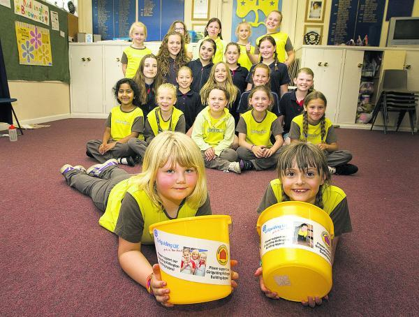 The Oxford Times: Kidlington Guides, Brownies and Rangers are trying to raise £300,000 for a new centre. Pictured, front, with collecting buckets are Katie King, seven, and Holly Morgan, seven. Picture: OX68323 Antony Moore