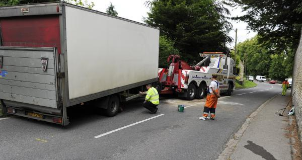 A recovery crew prepares to remove the damaged lorry