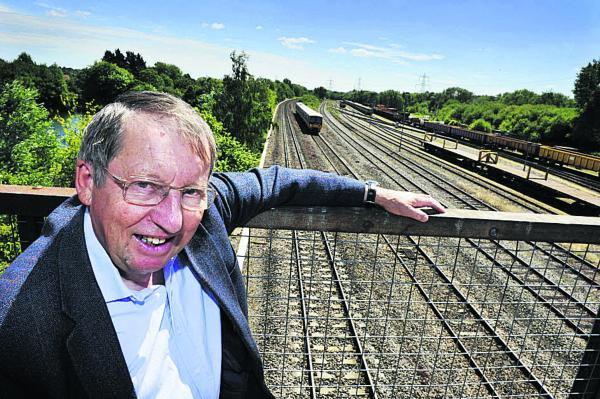 Cllr Bob Johnston stands above the rail track at South Hinksey that needs to be raised by a metre to prevent flooding