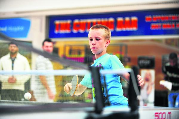 First time table tennis player Jacub Smith tries his luck against a machine