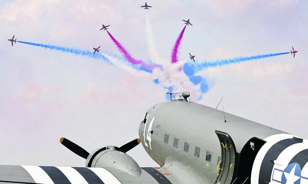 The Red Arrows split while trailing the famous red, white and blue smoke as they are pictured manoeuvering ahead of a Dakota C-47A Skytrain