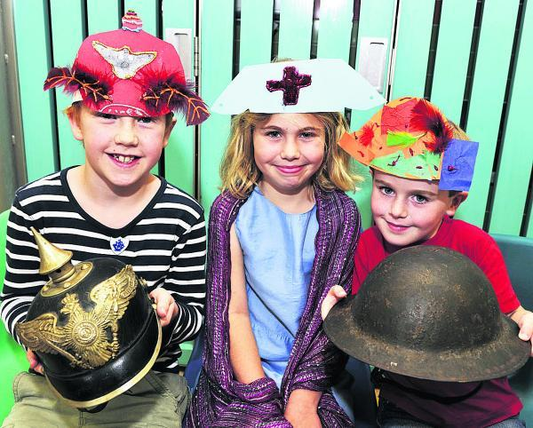 Adam Bradley, nine, with German Pickelhaube, Chloe Poulter, eight, with nurse's headress and Will Poulter, five, with British Brodie pattern helmet