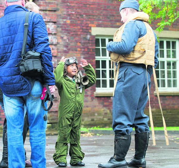 Six-year-old Rhys Elliott-Smith wearing an RAF Fighter Pilot's flight suit and his great uncle's leather flying helmet