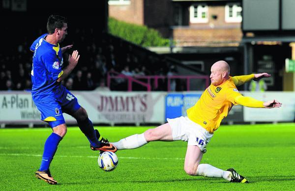 Andy Whing makes a tackle against AFC Wimbledon last season, when he was struggling for fitness
