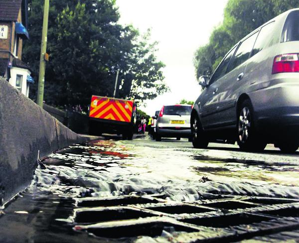 Cars drive through the water leak on Botley Road in Oxford. Picture: Neil Braggins