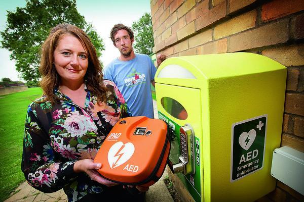 Nikki Rouse Thompson, whose husband died while playing football at Burwell Meadow in Witney, has had a defibrillator installed there. She is pictured with Paul's brother, Matthew Thompson    Main picture: OX69372 Damian Halliwell