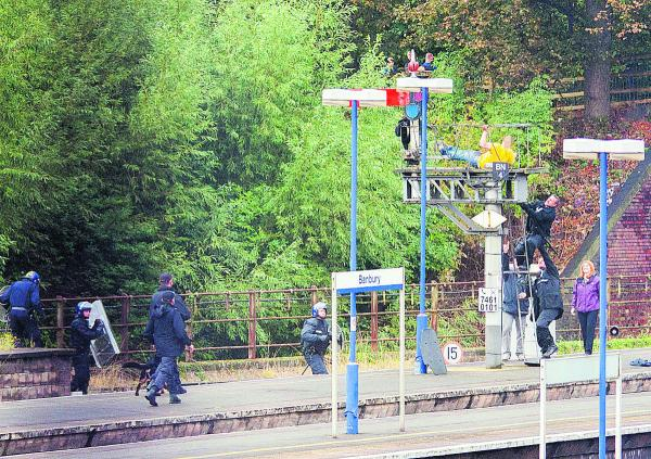 The man threatens to jump, harming himself as a police officer climbs to help at Banbury train station
