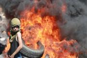A Palestinian boy looks on near burning tyres during clashes with Israeli soldiers following a protest in the West Bank village of Kofr Qadom