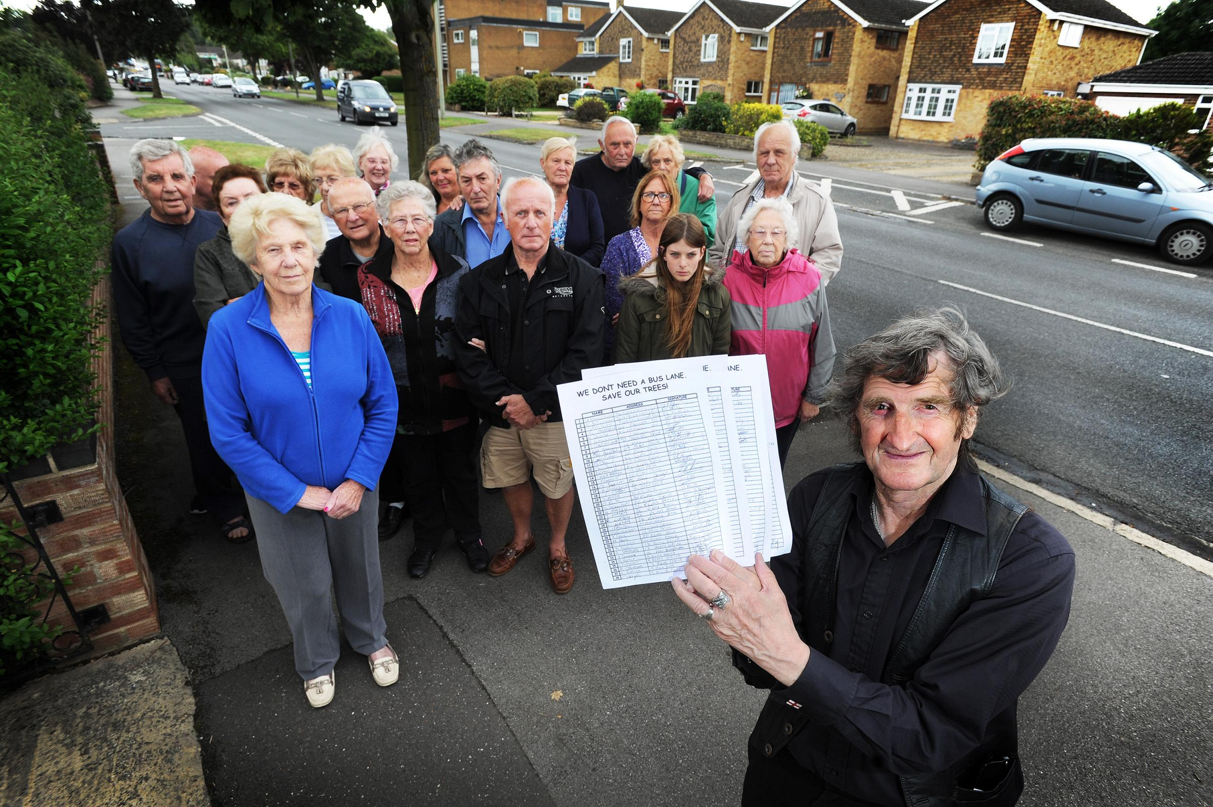 Opposition: Mick Haines, front, with a petition and residents against plans for a bus lane in Cherwell Drive