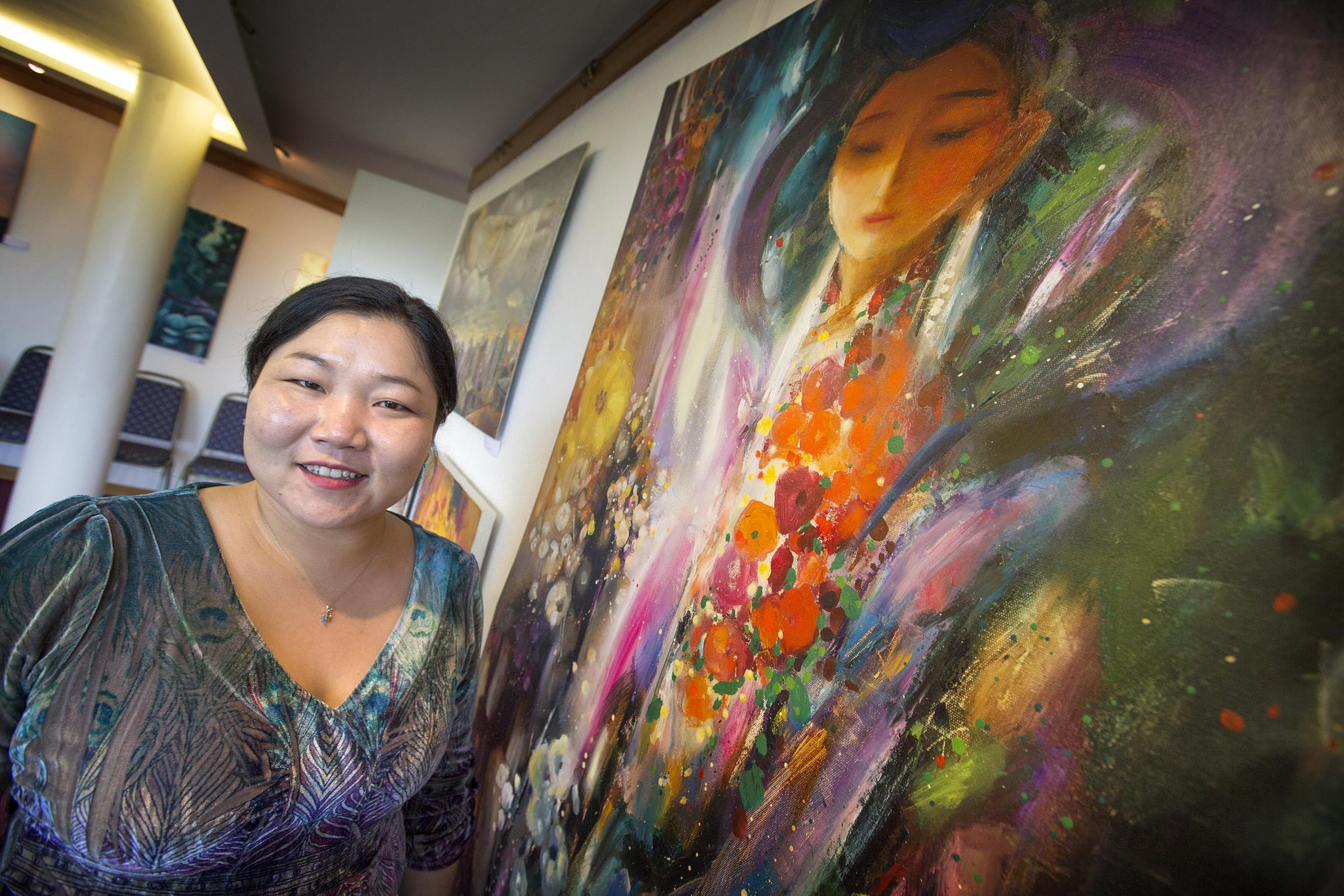 Soyolmaa Davaakhuu with her paintings at the Spirit of Mongolia exhibition