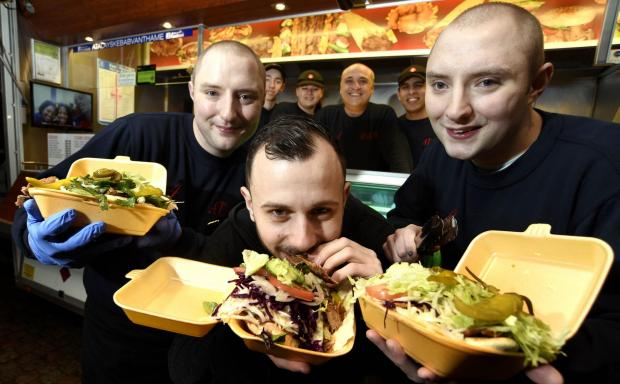 The Oxford Times: TUCKING IN: Kebab lover, Dom Stanway-Williams, enjoys a kebab from Atalay's Kebab van watched by Jason Atalay, and Joshua Atalay.
