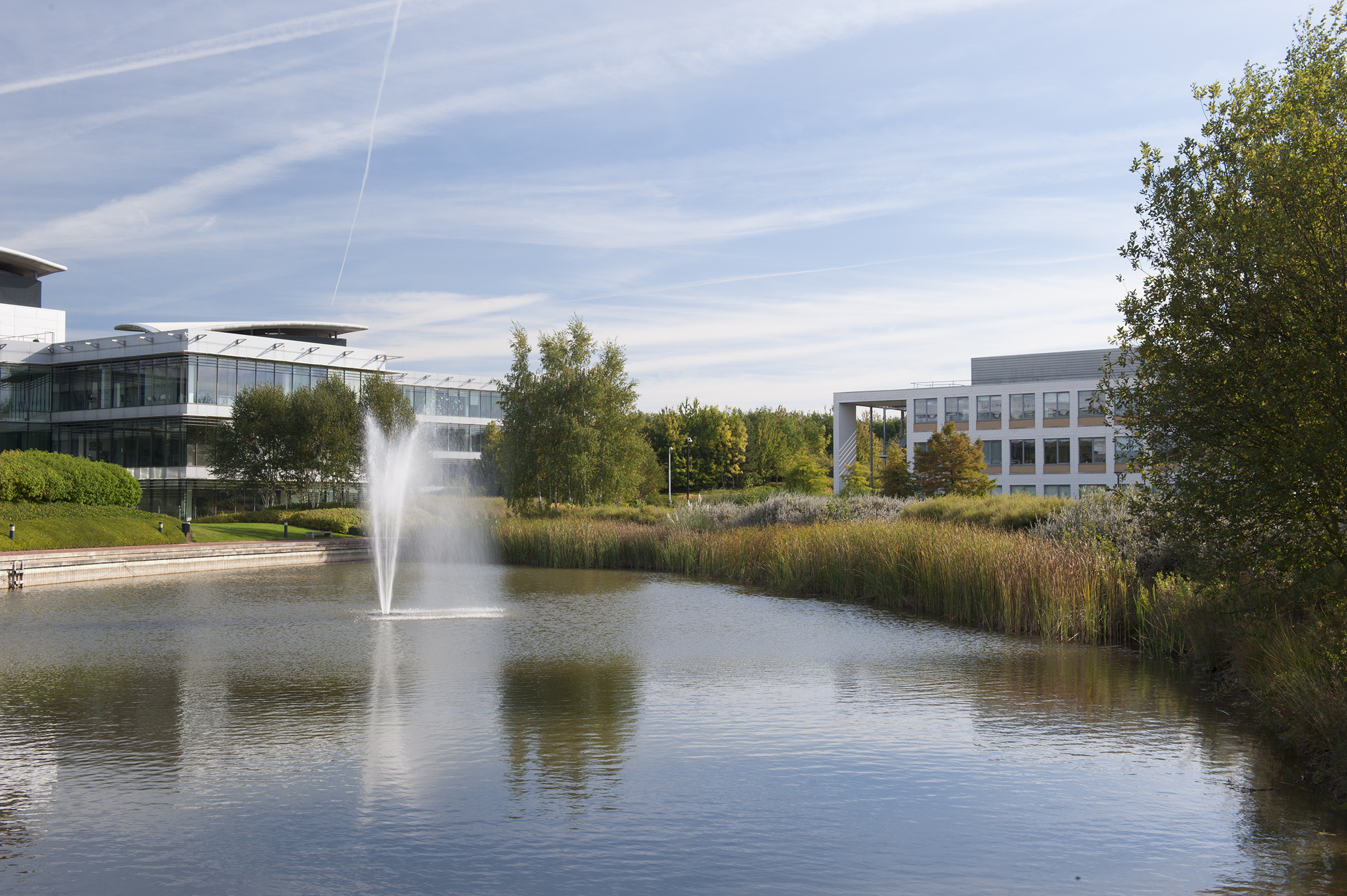 Oxford Science Park lake and fountain with businesses in the background