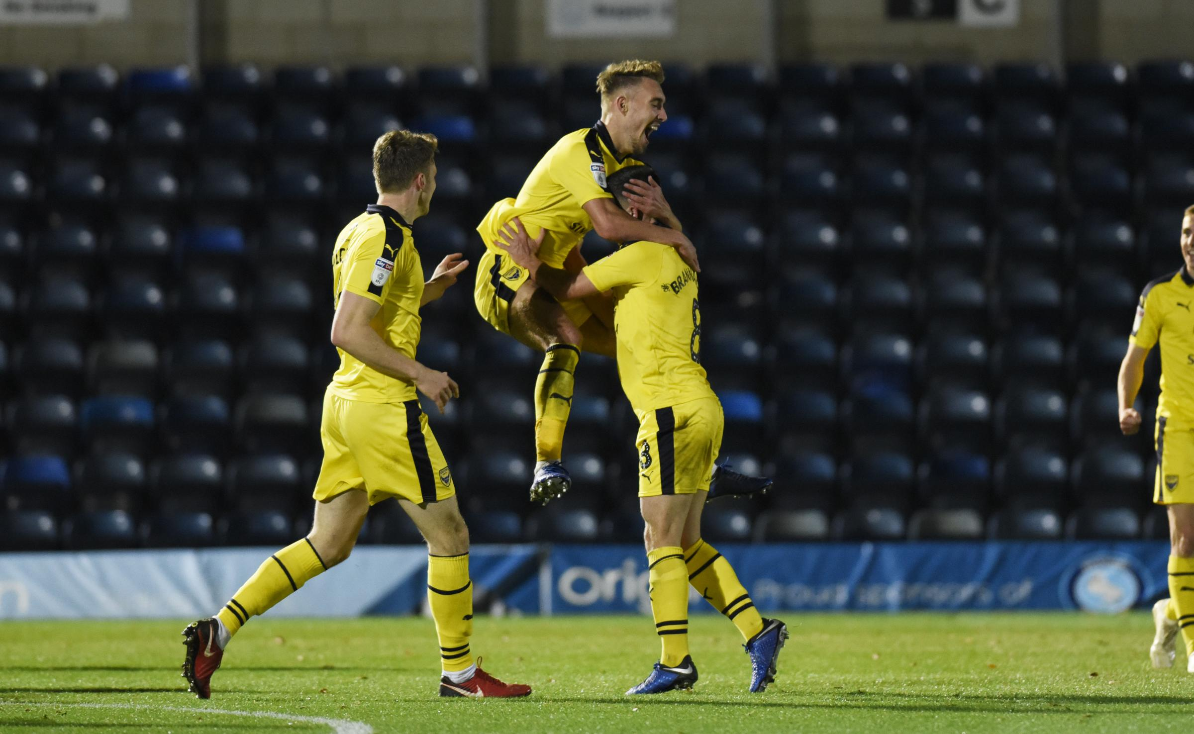 Sam Smith (centre) celebrates scoring Oxford United's third goal at Adams Park  Picture: David Fleming