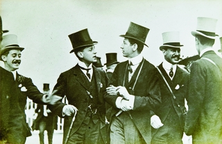 James de Rothschild (centre right) and friends celebrating Bomba's 1909 Ascot Gold Cup Win. Below, a newspaper cutting shows James and Dorothy de Rothschild arriving at the races.    Waddesdon, The Rothschild Collection (The National Trust)